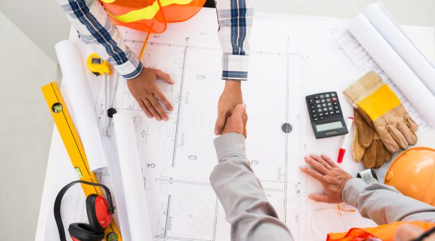 Contractor and engineer shaking hands over blueprint of building