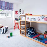 Children's room with star shape bunting strung along wooden bunk bed with red painted chair by desk and blue and red striped Roman blinds